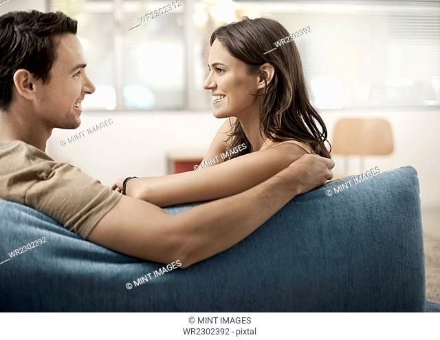 A young couple sitting on a sofa, gazing at each other, a man and woman, boyfriend and girlfriend