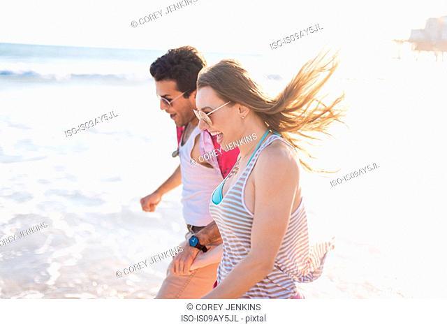 Young couple paddling in sea, Santa Monica, California, USA