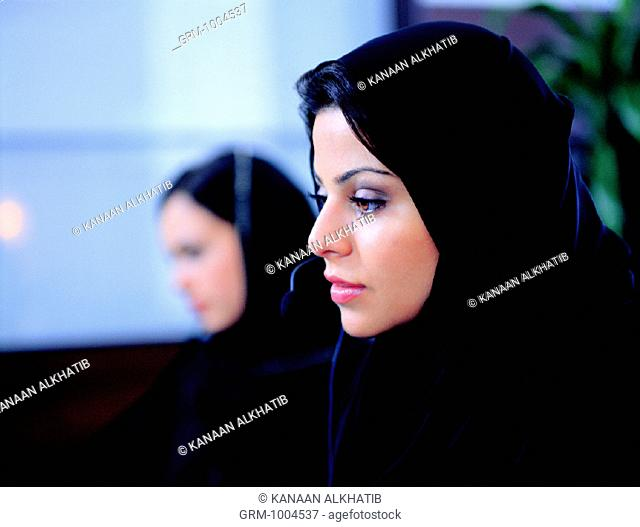 Arab women wearing telephone headsets