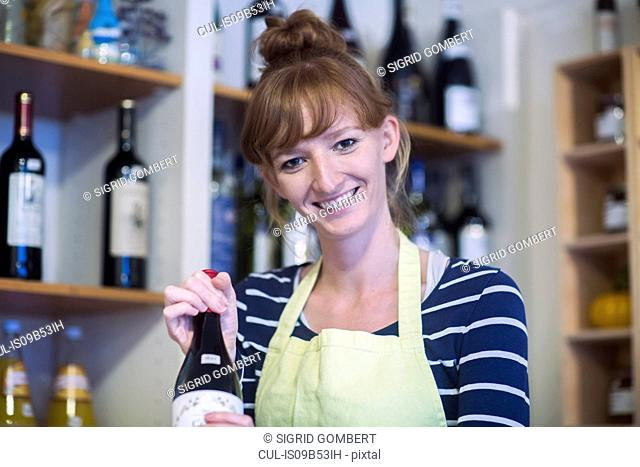 Portrait of young woman in shop, holding bottle of wine
