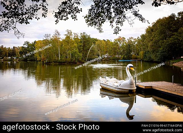 16 October 2021, Lower Saxony, Burgwedel: A pedal boat in swan optics lies in the morning in cloudy weather at a jetty in the Springhorstsee in the region of...