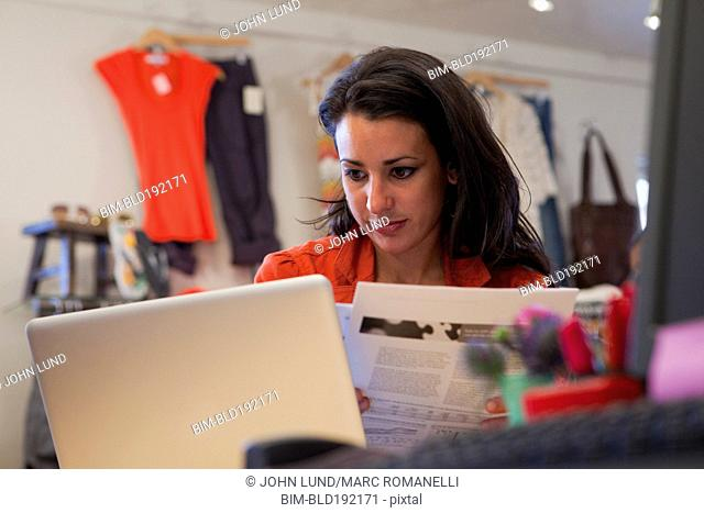 Hispanic business owner using laptop in clothing store