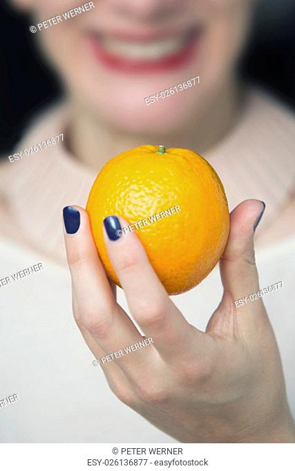 woman holding an orange in her hand and smiles