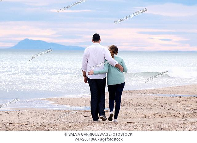 Bridal couple walking along the beach holding each saler, Valencia, Spain, Europe
