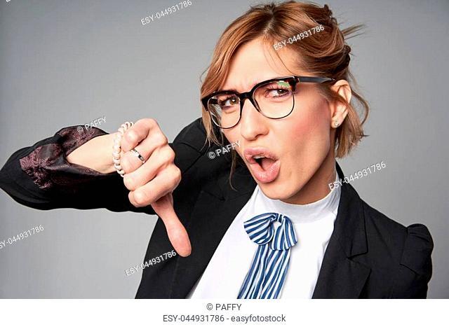 Emotional funny business woman gesturing thumb down, studio portrait