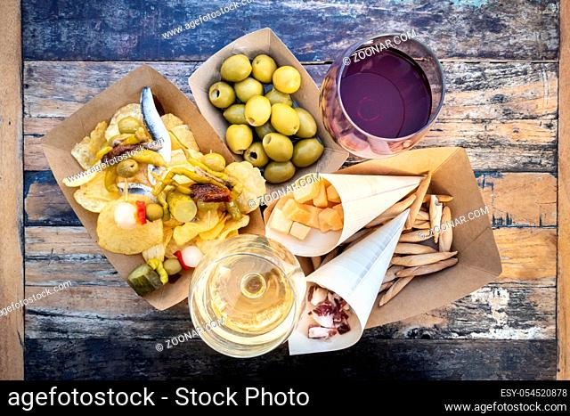 Tapas and pinchos, shot from above. Cheese, jamon and olives, gildas and potato chips, with glasses of red and white wine, on a wooden table in an outdoors cafe