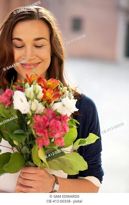Smiling woman smelling bouquet of flowers