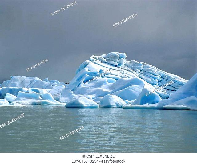 A bright iceberg with dark clouds