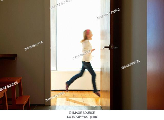 Girl running past doorway