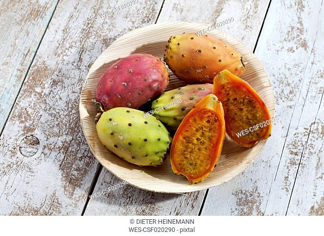 Sliced and whole prickly pears (Opuntia ficus-indica) on plate made from palm leaves on white wooden table, studio shot