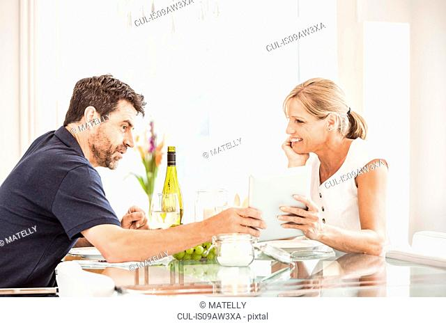 Mature couple sitting at table, looking at digital tablet