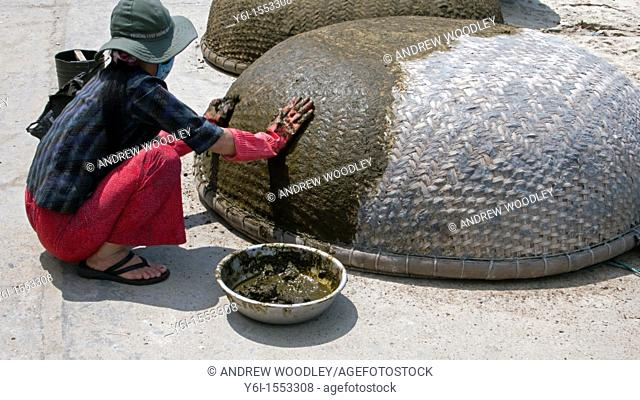 Woman seals traditional circular woven coracle boats Cham Island off historic Hoi An Vietnam