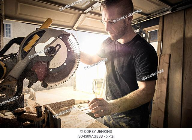 Male carpenter working with a rotary saw in workshop