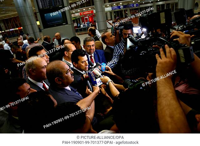 01 September 2019, Egypt, Cairo: Egyptian Youth and Sports minister, Ashraf Sobhy (C), speaks to the media upon his arrival to welcome the Egyptian athletic...