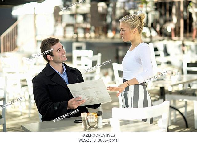 Man and waitress at outside restaurant