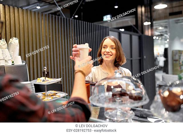 small business, people and service concept - happy woman taking coffee cup from seller at vegan cafe