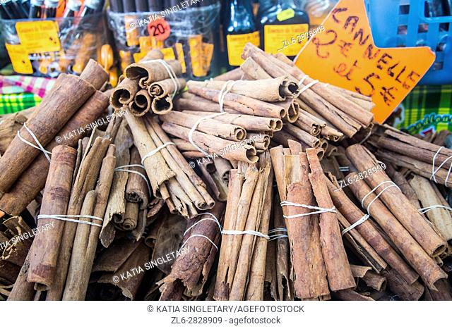 Cinnamon sticks bundle together for sale in a Martinique market. They are for sale for 2 Euros a pack