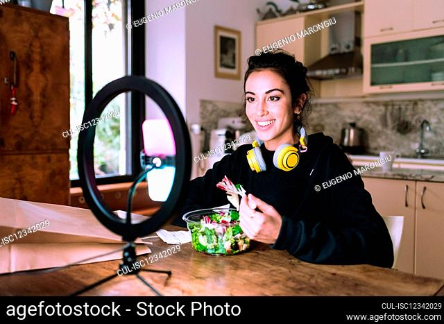Young woman having video call during lunch