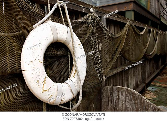 Old net and old lifebuoy are hanging on land