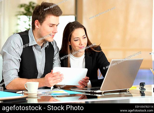 Two employees comparing tablet and laptop content