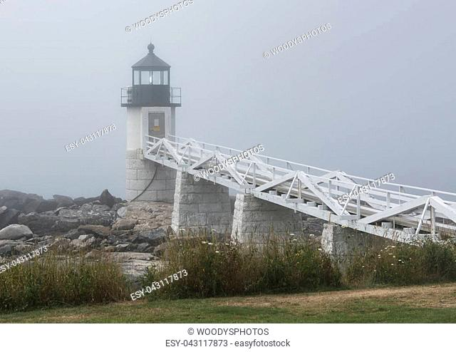 The Marshall Point Lighthouse has its light on during a very foggy summer morning