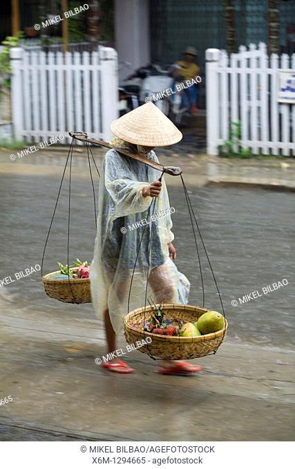 Hawker under the rain  Hoi An, Vietnam, Asia