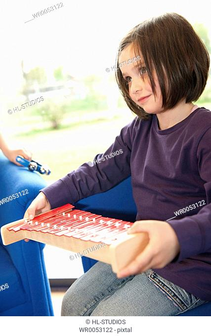 Little girl holding a xylophone