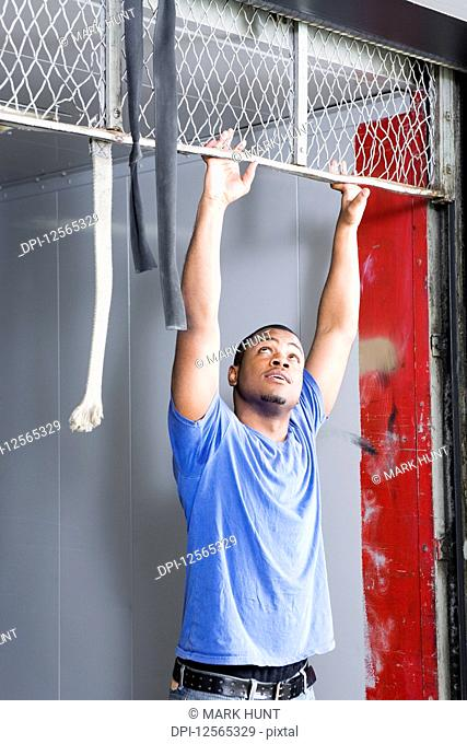 Young man holding on iron frame