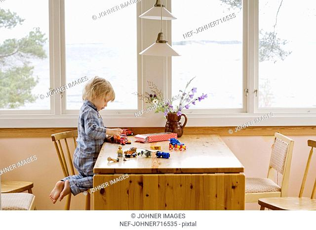 Boy playing with his toys on a table, Sweden