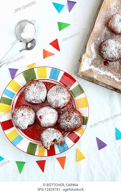 Jam doughnuts on a baking tray and on a colourful plate with a string of bunting