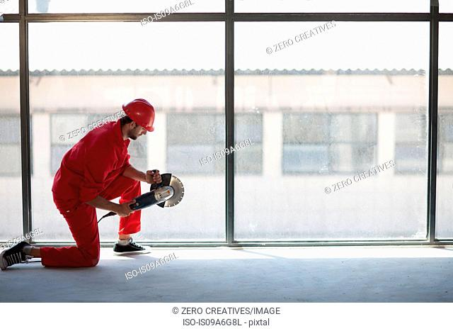 Laborer kneeling in front of window with circular saw