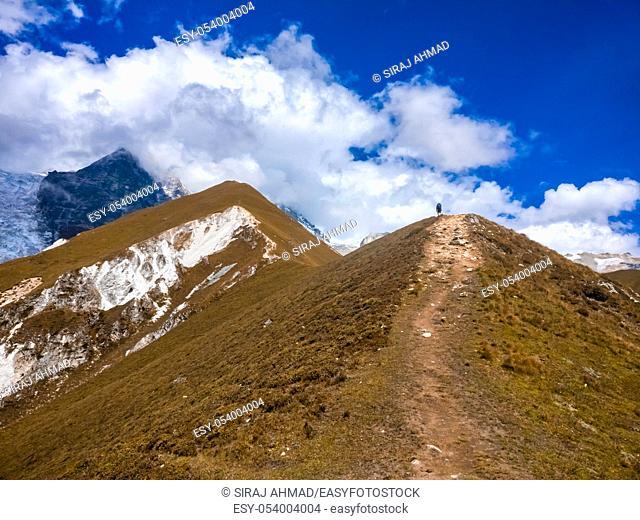 Guy hiking towards Upper Kyanjin Ri peak (4800 m. ) in Langtang National Park, Nepal