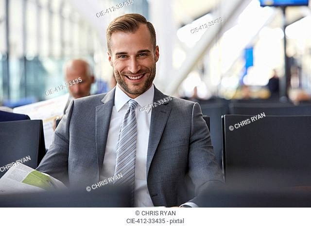 Portrait smiling businessman reading newspaper in airport departure area