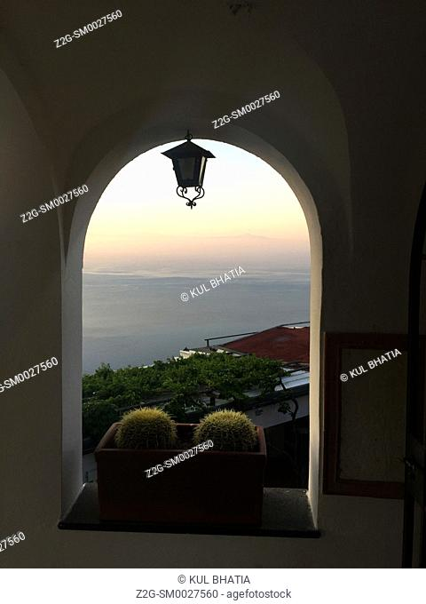 An iconic image of the Amalfi Coast through an archway in Ravello, Italy