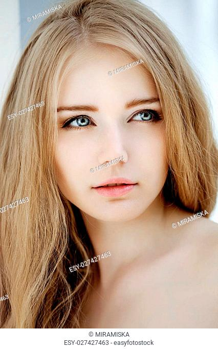 Woman face close up. A pretty young blond trendy. Girl with a beauty face. Beautiful female face with luxury make-up