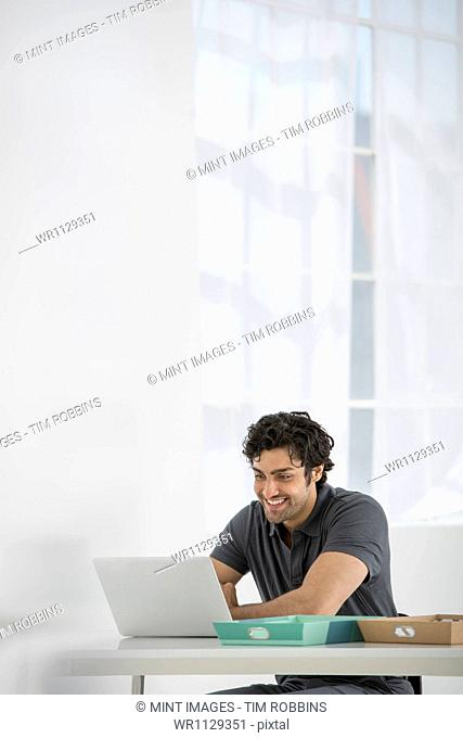 An office in the city. Business. A man sitting at a desk using a laptop