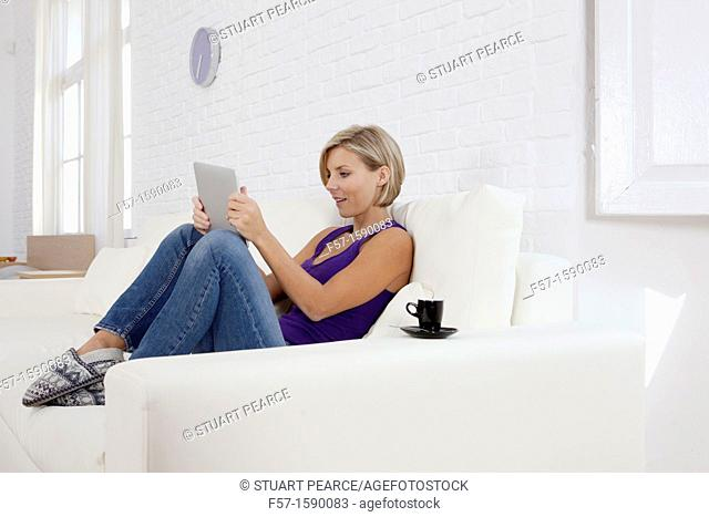 Woman relaxing on her sofa with her tablet computer