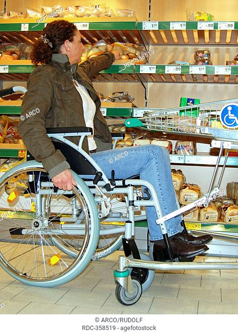 Wheelchair user in supermarket, accessible supermarket trolley, shopping cart