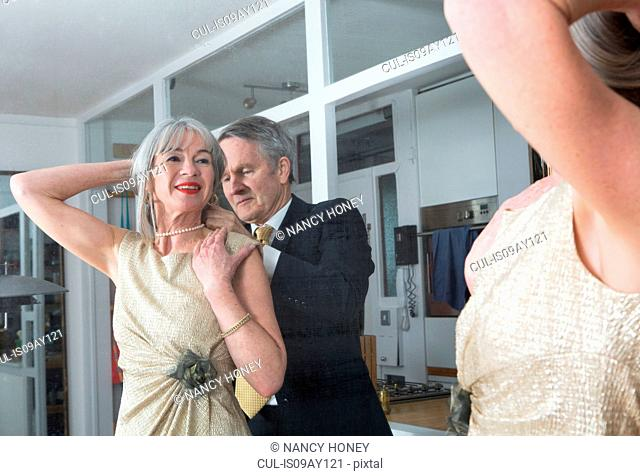 Couple dressing up getting ready in front of mirror