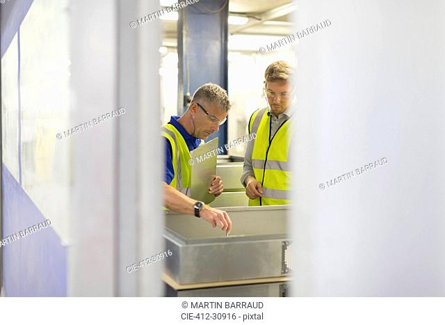 Supervisor and worker inspecting pieces in steel factory