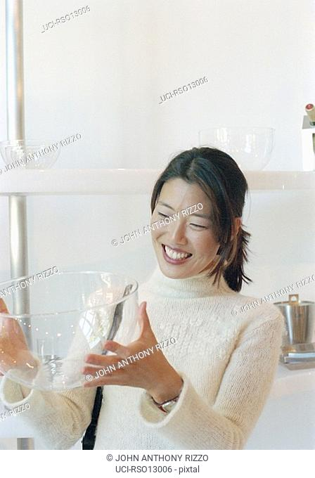 Asian woman holding glass bowl