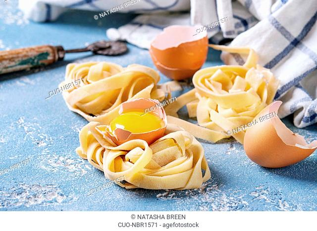 Fresh raw uncooked homemade pasta tagliatelle twisted with egg yolk, shell and pasta cutter with kitchen towel over light blue concrete background