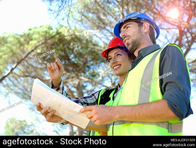 Female engineer discussing with male colleague holding document