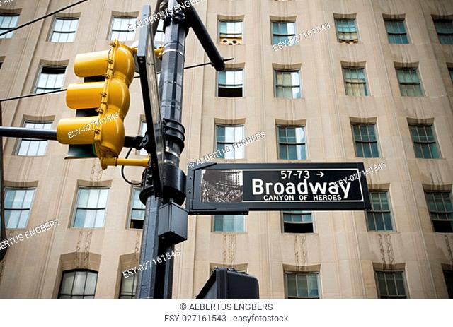 broadway street sign with yellow traffic lights in new york city