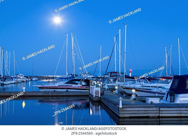 Yachts at the Bronte Outer Harbour Marina at dusk during the full moon. Bronte, Oakville, Ontario, Canada