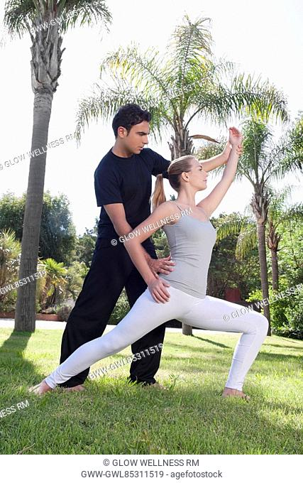 Man assisting a woman in exercise