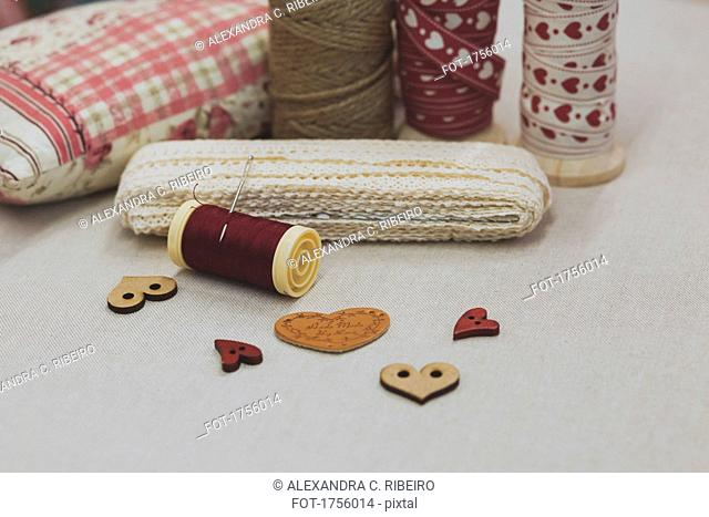 Close-up of various lace and spool with heart shape buttons on fabric