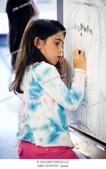 Girl drawing on easel in art class