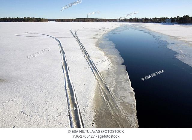 snowmobile trails on melting ice, Finland
