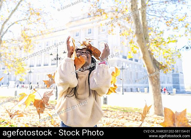 beautiful african girl playing with leaves in the park
